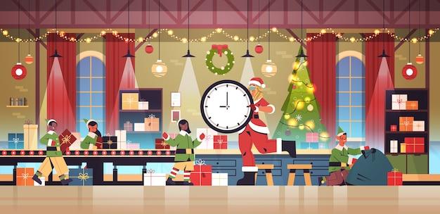 Santa, mujer, tenencia, reloj, mezcla, raza, elfos, poniendo, regalos, en, transportador, año nuevo, navidad, celebración, concepto, taller, interior, horizontal, longitud completa, vector, ilustración