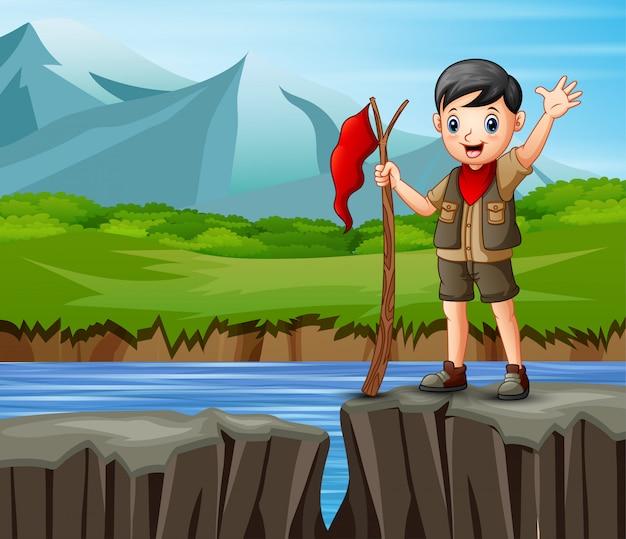 Scout boy parado al borde de un acantilado con una hermosa vista