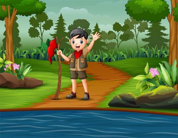 Scout boy sosteniendo la bandera roja en el camino