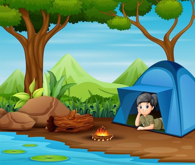 Scout girl en carpa azul y ver la vista a su alrededor
