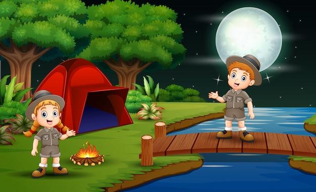 Scout niño y niña acampan en la naturaleza por la noche