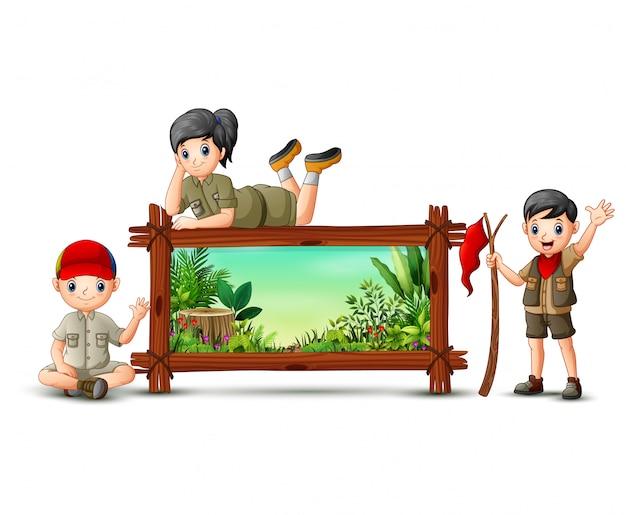 Scout niño y niña cerca del marco de madera