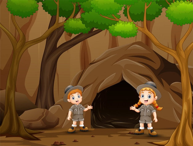 Scout niño y niña hablando cerca de la cueva
