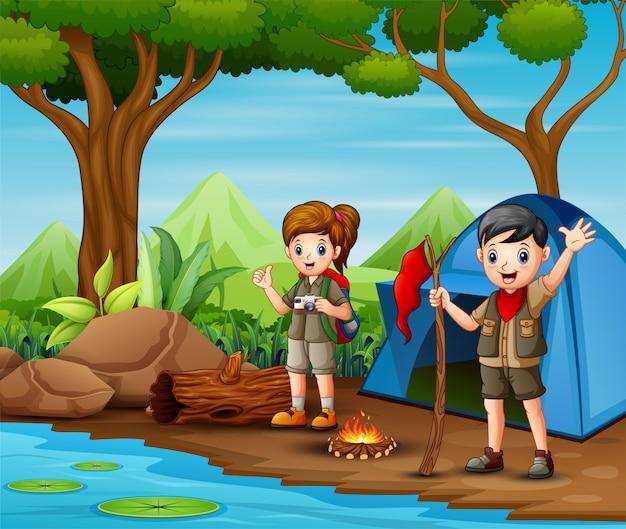 Scout niño y niña en uniforme explorando el bosque