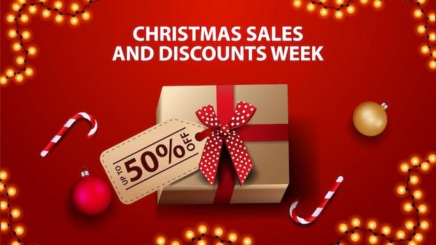 Semana de descuentos y ventas navideñas, pancarta roja con caja de regalo, bolas navideñas y bastón de caramelo, vista superior