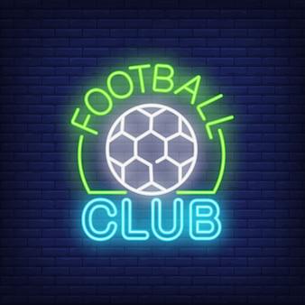 Señal de neón del club de fútbol. forma de balón de fútbol en el fondo de la pared de ladrillo.