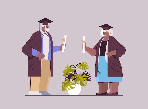 Senior hombre mujer estudiantes graduados de pie juntos graduados de edad celebrando el título de diploma académico