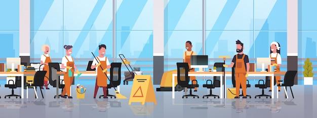 Servicio de limpieza del equipo de conserjes limpiadores masculinos femeninos en uniforme trabajando junto con equipos profesionales moderno centro de trabajo compartido interior de la oficina