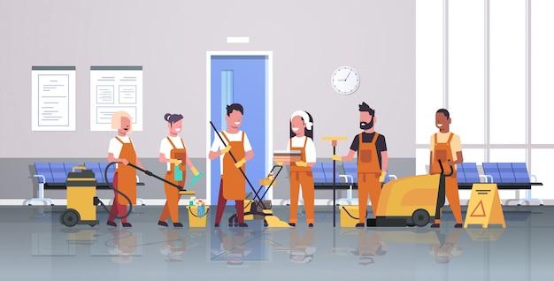 Servicio de limpieza del equipo de conserjes limpiadores masculinos femeninos en uniforme trabajando juntos con equipos profesionales interior moderno corredor