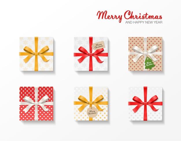 Set de caja de regalo cuadrada. nudo de lazo dorado, rojo, plateado, cintas, bola kraft y etiquetas colgantes de árbol. patrón de copo de nieve, papel viejo. texto feliz navidad