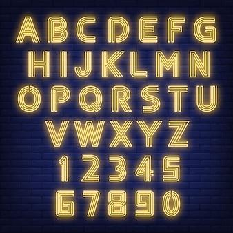 Signo de neón del alfabeto inglés. letras y figuras que brillan intensamente en fondo oscuro de la pared de ladrillo.