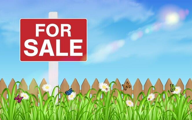 Signo de venta de tierra en campo de hierba con fondo de cielo