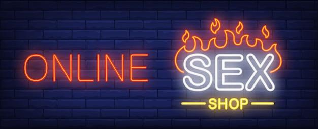Signo de neón de la tienda de sexo en línea. palabra de fuego o pared de ladrillo oscuro.