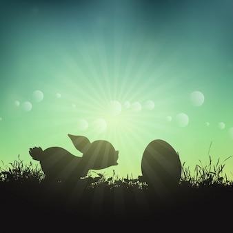 Silueta de un conejo de pascua y huevo en el paisaje cubierto de hierba