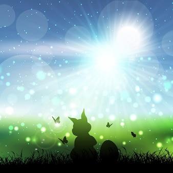 Silueta de un conejo de pascua en un paisaje cubierto de hierba