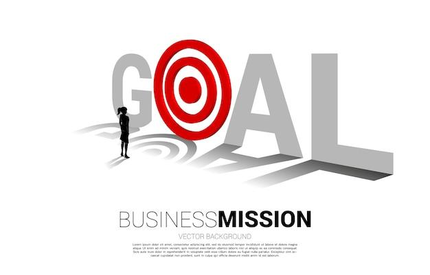 Silueta de empresaria para apuntar diana en palabra objetivo. concepto de visión, misión y objetivo empresarial.
