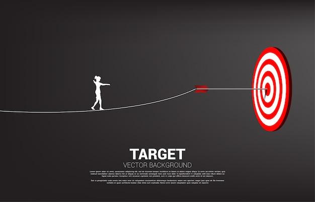 La silueta de la empresaria camina la cuerda al tiro con arco de la flecha golpeó en el centro del blanco. concepto de focalización y desafío empresarial.