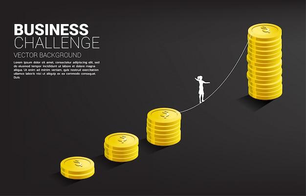 Silueta de empresaria caminando en forma de caminata de cuerda al gráfico de pila de monedas de oro. concepto de riesgo y desafío empresarial.