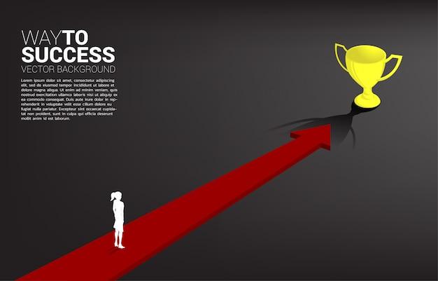 La silueta de la empresaria en flecha se mueve al trofeo de oro. concepto de dirección comercial y visión de misión.
