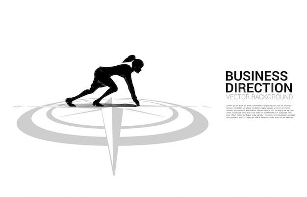 Silueta de empresaria lista para correr desde el centro de la brújula en el piso. concepto de trayectoria profesional y dirección comercial