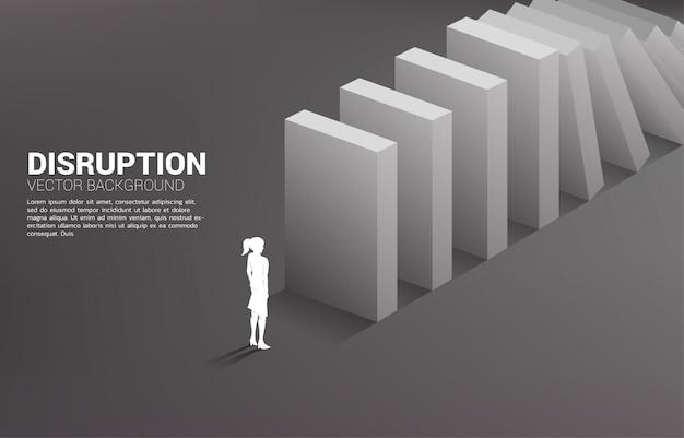 Silueta de empresaria de pie al final del colapso dominó. concepto de perturbación de la industria empresarial