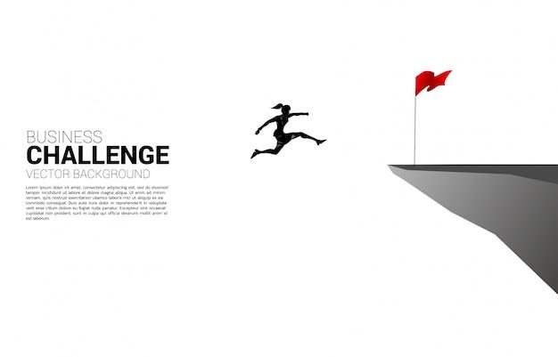 Silueta de empresaria saltando a la bandera en el acantilado. concepto de negocio de focalización y rumbo al cliente.