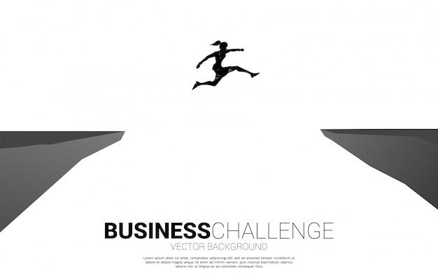 Silueta de empresaria saltando sobre la brecha del valle. concepto de riesgo de desafío empresarial.