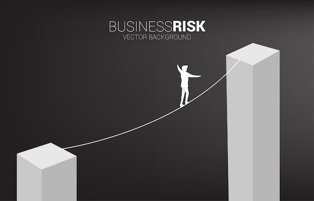 Silueta del empresario caminando en forma de cuerda a pie a un gráfico de barras más alto.