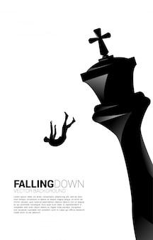 Silueta de empresario cayendo del ajedrez rey. concepto de estrategia empresarial y situación de fracaso.