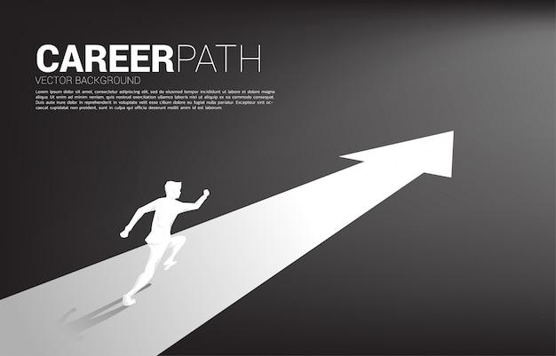 Silueta de empresario corriendo en flecha hacia adelante.