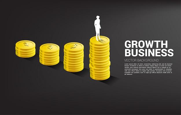 Silueta de empresario de pie encima del gráfico de crecimiento con pila de monedas