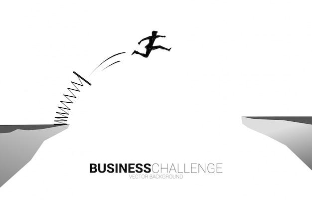 Silueta del empresario saltar sobre la brecha con trampolín. concepto de impulso y crecimiento en los negocios.