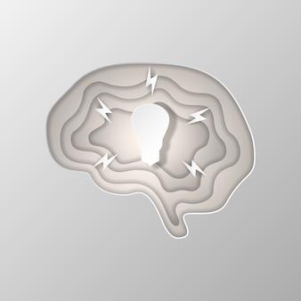 Silueta gris del cerebro tallada en papel.