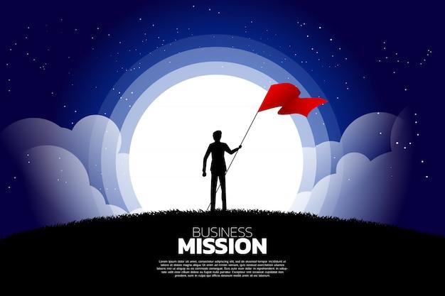 Silueta del hombre de negocios con la bandera que se coloca en la luna y la estrella.