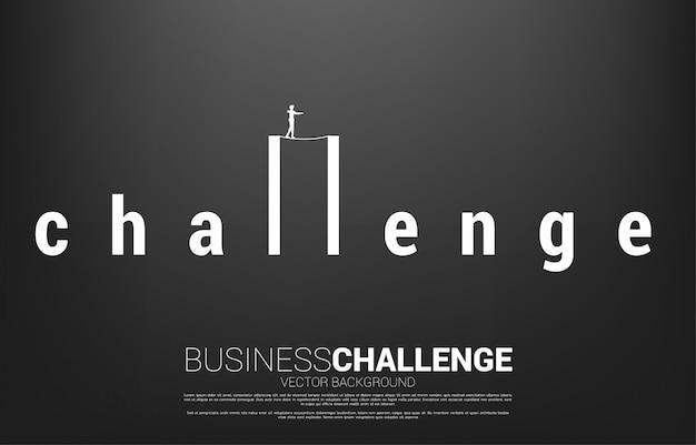 Silueta de hombre de negocios caminando por la cuerda a pie en la redacción del desafío. concepto de riesgo empresarial y desafío en la carrera