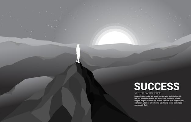 Silueta de un hombre de negocios en la cima de la montaña