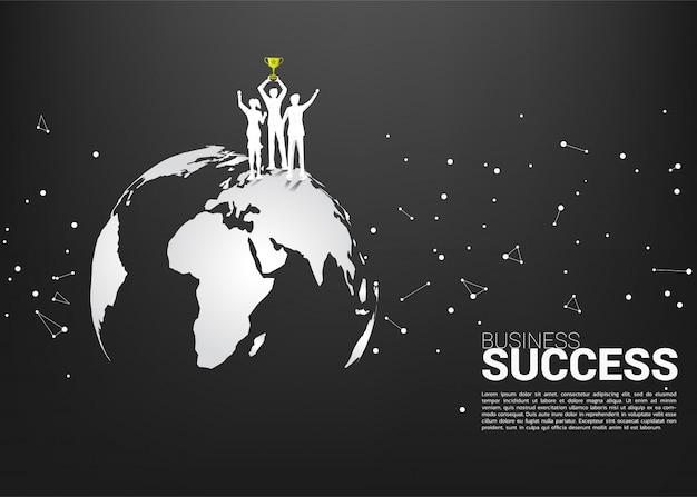 Silueta del hombre de negocios y de la empresaria con el trofeo del campeón que se coloca en mapa del mundo