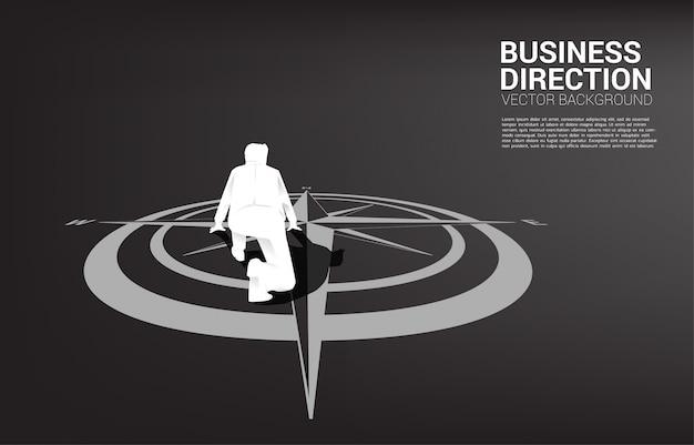 Silueta de hombre de negocios listo para correr desde el centro de la brújula en el piso.