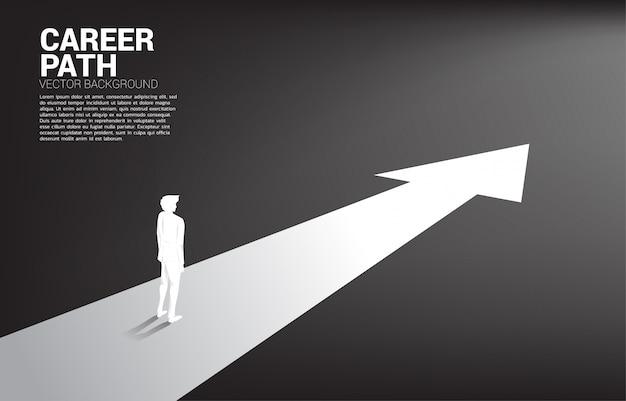 Silueta de hombre de negocios de pie en la flecha hacia adelante.