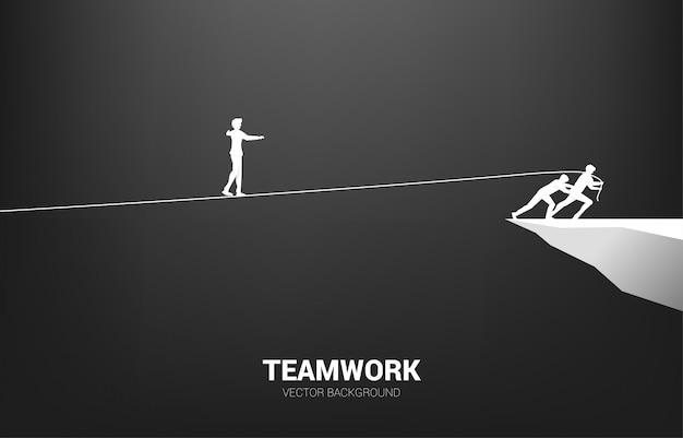 Silueta del hombre de negocios que camina en el camino de la cuerda tirado por el equipo. concepto para el trabajo en equipo y el apoyo del equipo.