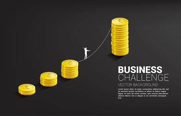 Silueta del hombre de negocios que camina en manera del paseo de la cuerda al gráfico de oro de la pila de monedas. concepto para el riesgo y el desafío del negocio