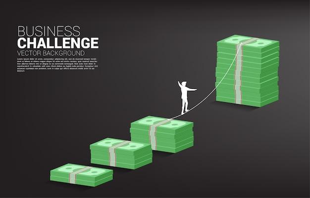 Silueta del hombre de negocios que camina en manera del paseo de la cuerda al gráfico de la pila del billete de banco del dinero. concepto para el riesgo y el desafío del negocio.
