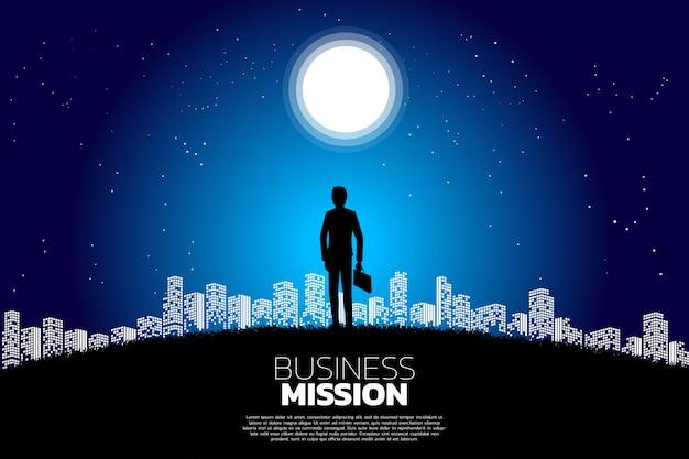 Silueta del hombre de negocios que se coloca en la luna y la estrella.