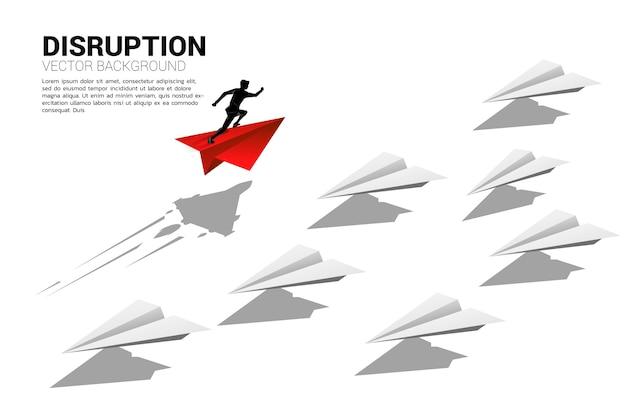 La silueta del hombre de negocios que se ejecuta en el avión de papel rojo del origami va de manera diferente del grupo de blancos. concepto de negocio de disrupción y misión de visión.