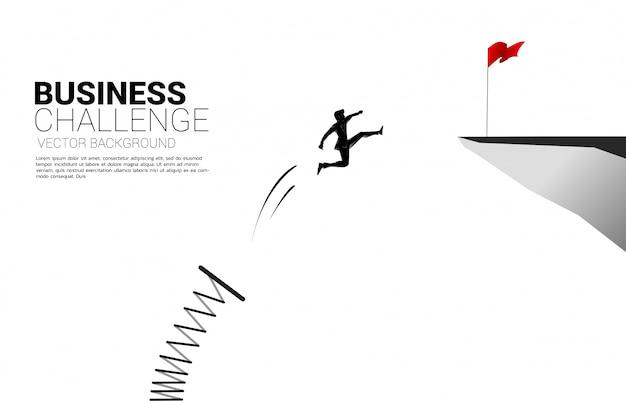 La silueta del hombre de negocios salta a la bandera roja en el acantilado con trampolín. concepto de impulso y crecimiento en los negocios.