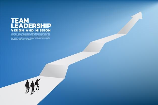 Silueta de un líder de equipo mirar hacia la flecha de crecimiento empresarial