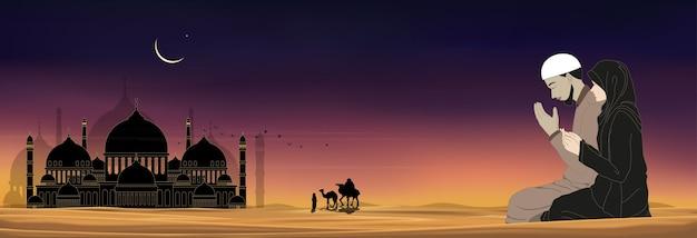 Silueta de mezquita con hombre y mujer musulmanes haciendo una súplica en el desierto