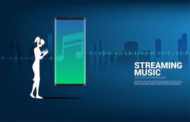 Silueta de mujer con auriculares y fondo de ecualizador de música de onda de sonido.