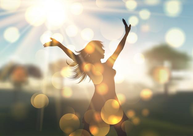 Silueta de mujer joven contra el paisaje desenfocado iluminado por el sol