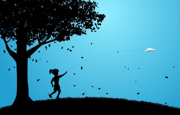 Silueta de niña corriendo para tirar aeroplano de papel de origami bajo un gran árbol.